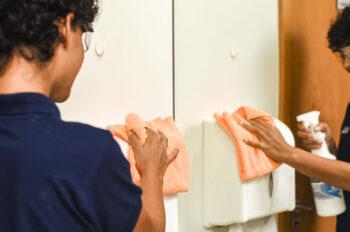 funcionária limpando o banheiro evitando a contaminação cruzada
