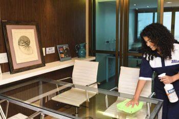 Vemos uma profissional fazendo a higienização de escritórios.