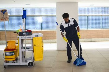 Profissional da RHS Premium utiliza pá e vassoura para limpar as áreas comuns do condomínio